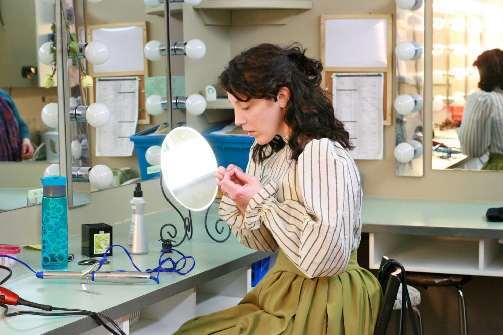 A stage actress putting on makeup