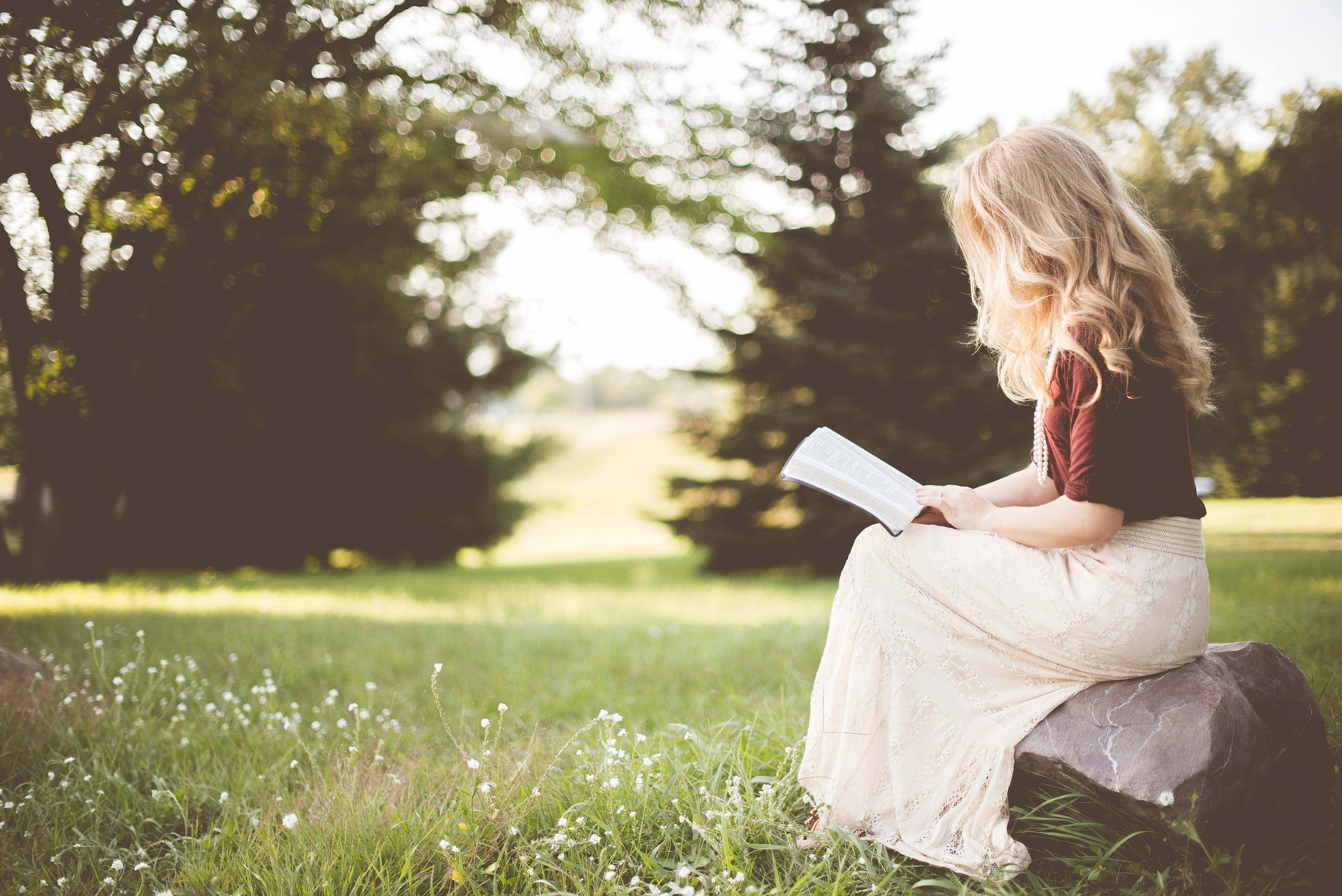 woman sitting outside while reading book