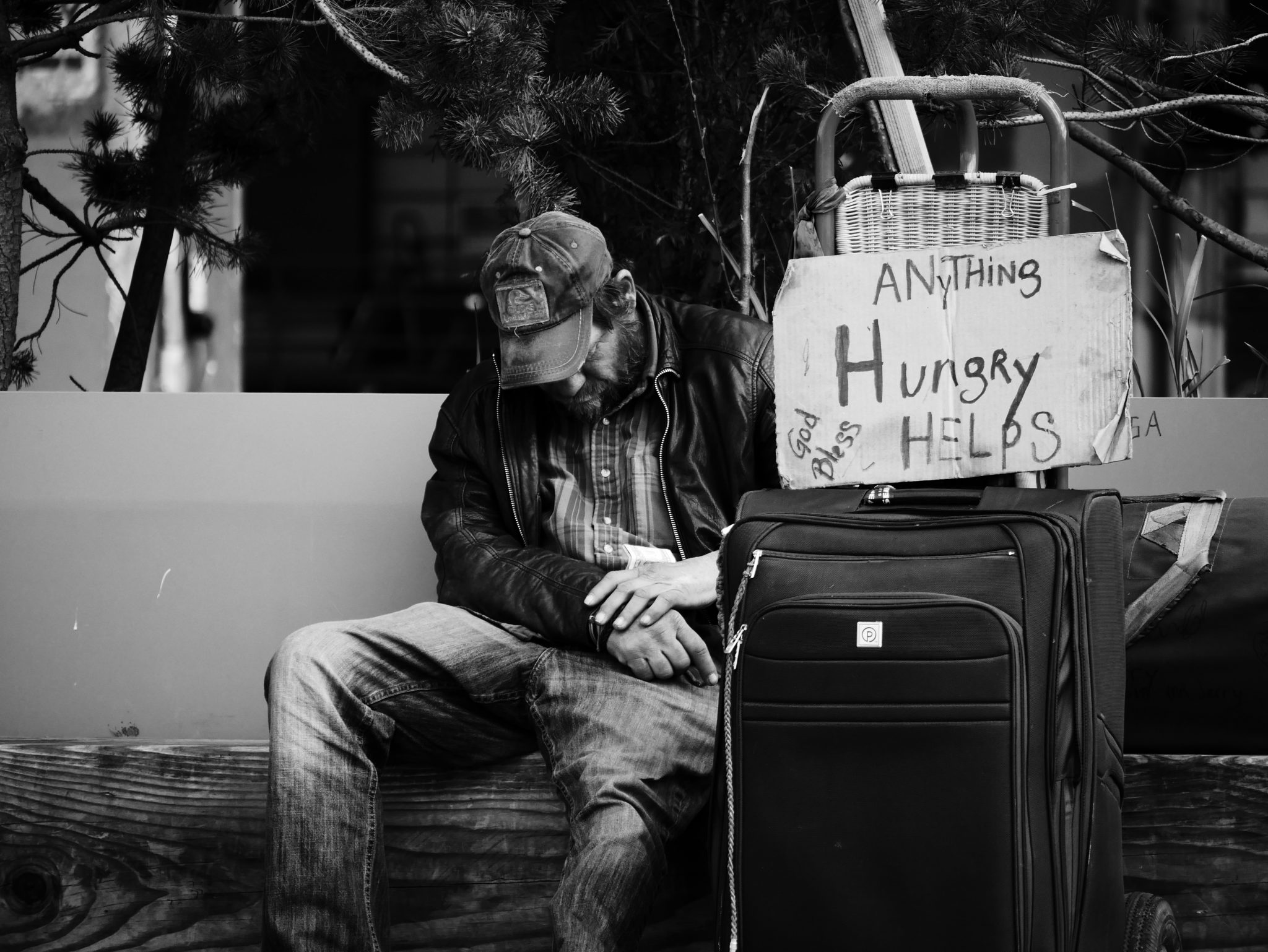 "homeless man with his head down, sign that says ""hungry, anything helps"""