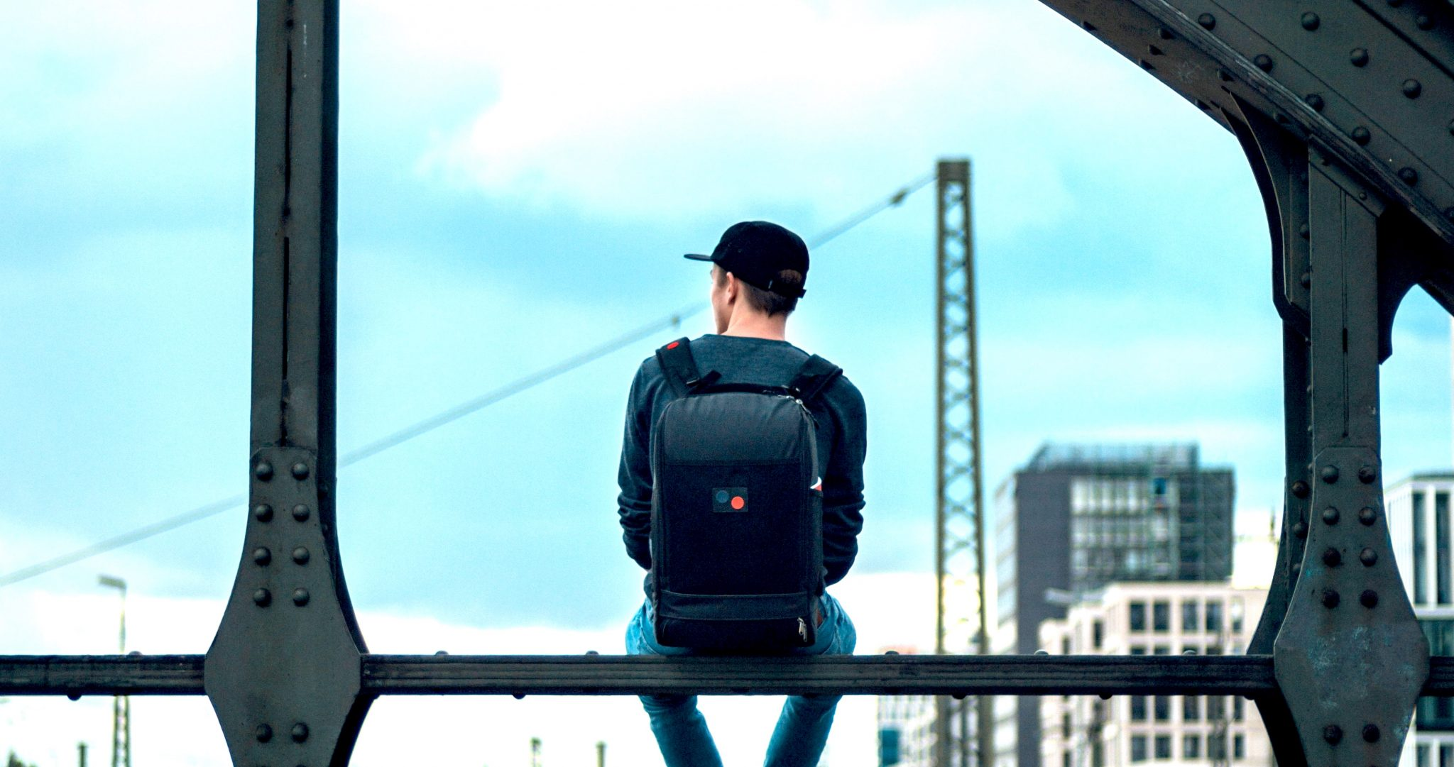 man wearing backpack, sitting on ledge facing out to city