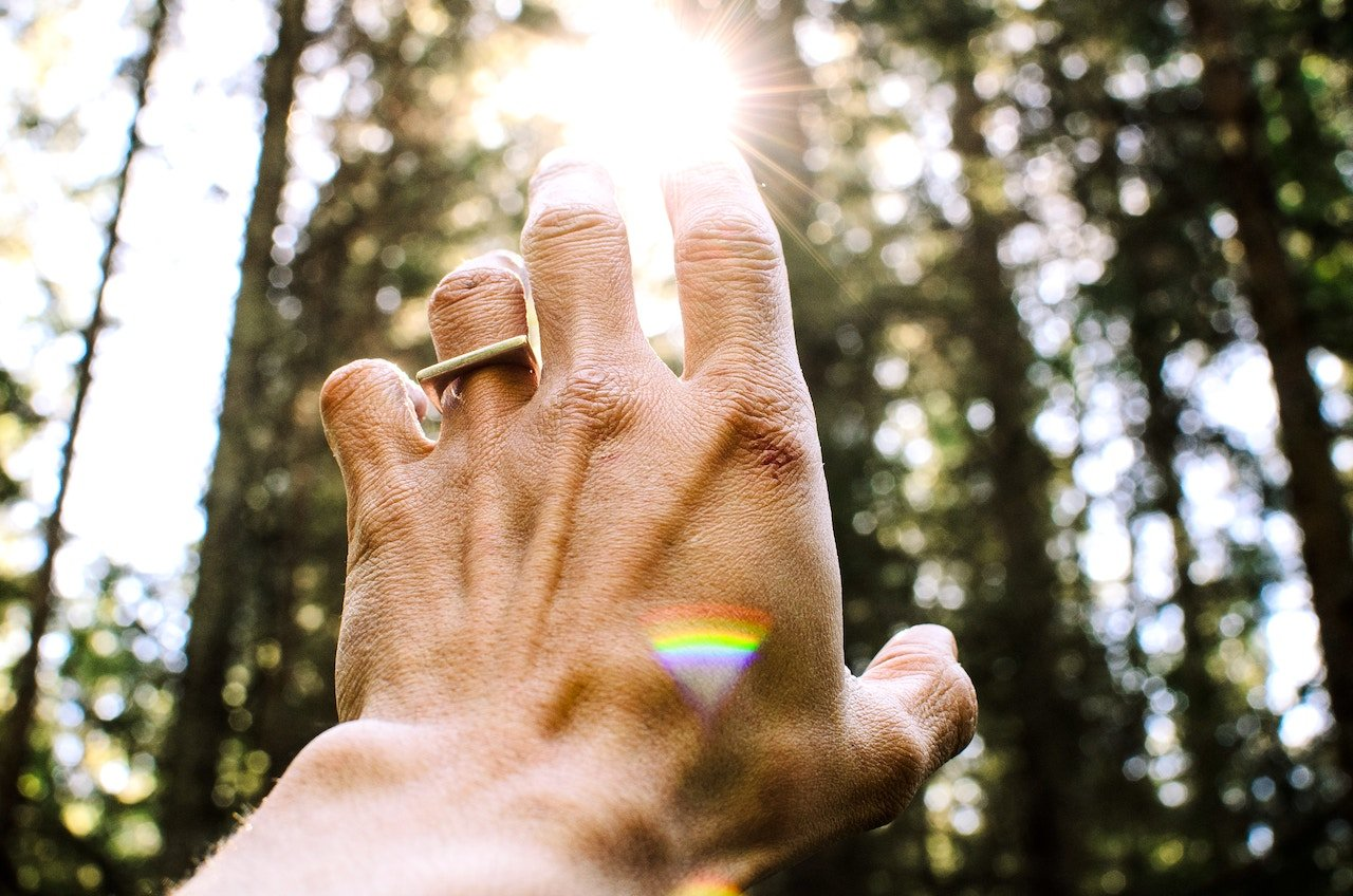 hand reaching for the sun shining through trees, with small rainbow reflection