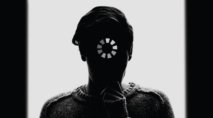 "silhouette of a person with ""loading"" symbol over their face"