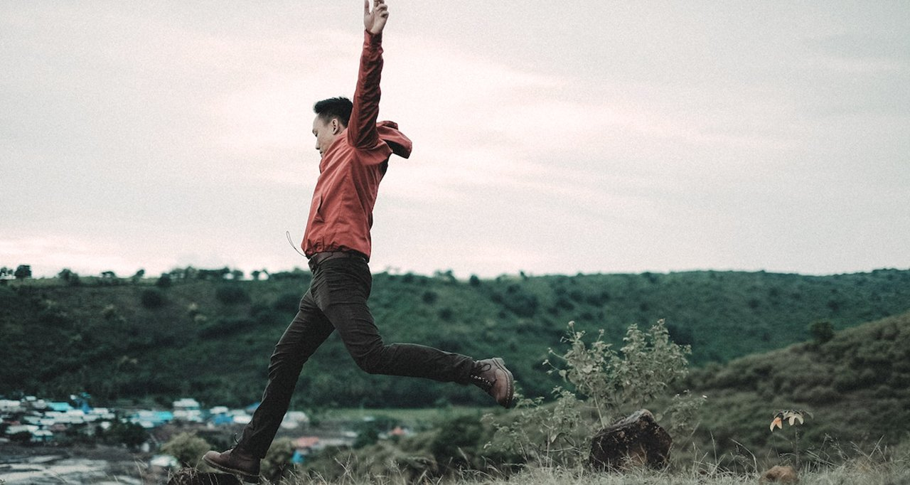Man, on a field jumping to a rock.